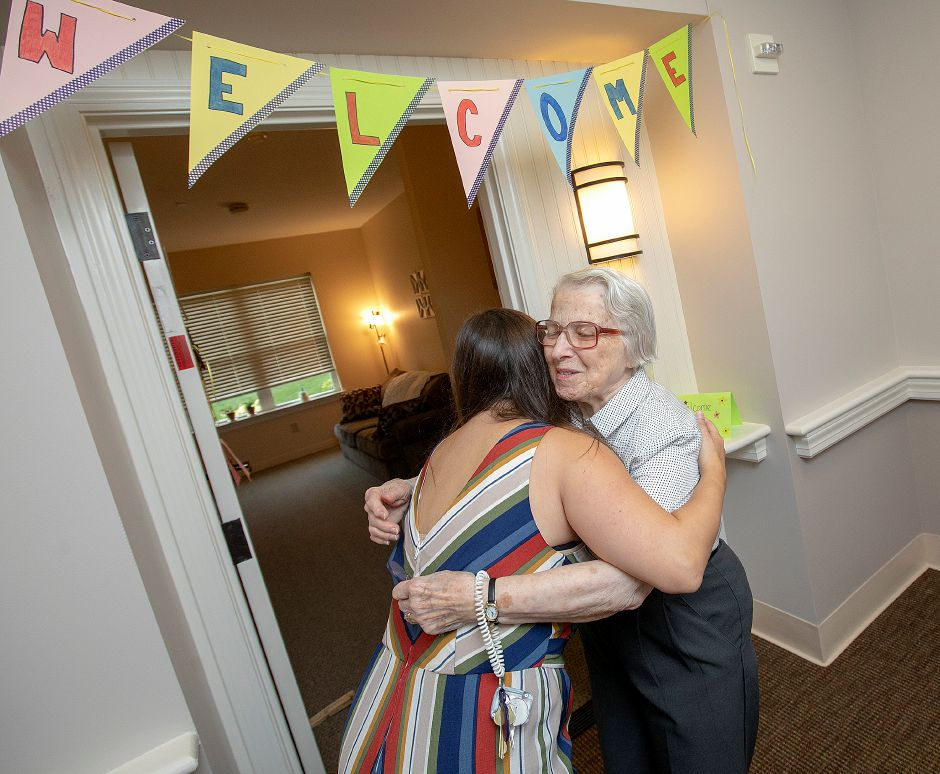 Quinnipiac University graduate student Julia Kowal gets a welcoming hug from resident Clarisse Miessau outside her new room at Ashlar Village.