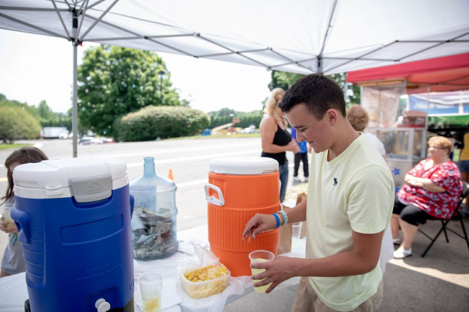 Nico Fasold drops a lemon slice into a glass of lemonade at his yearly lemonade stand to raise money for the Make a Wish Foundation. This year