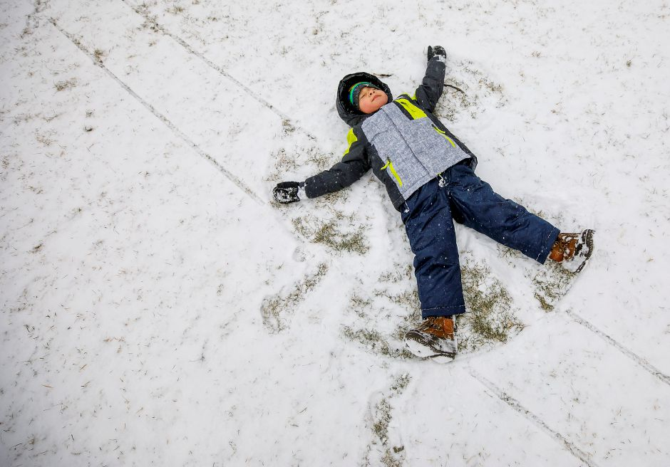 Matthew Gallosa, 3, of Plainville, makes a snow angel in light snow at Hubbard Park in Meriden, Tues., Jan. 26, 2021. Snow will continue into tonight bringing two to four inches of accumulation. Dave Zajac, Record-Journal