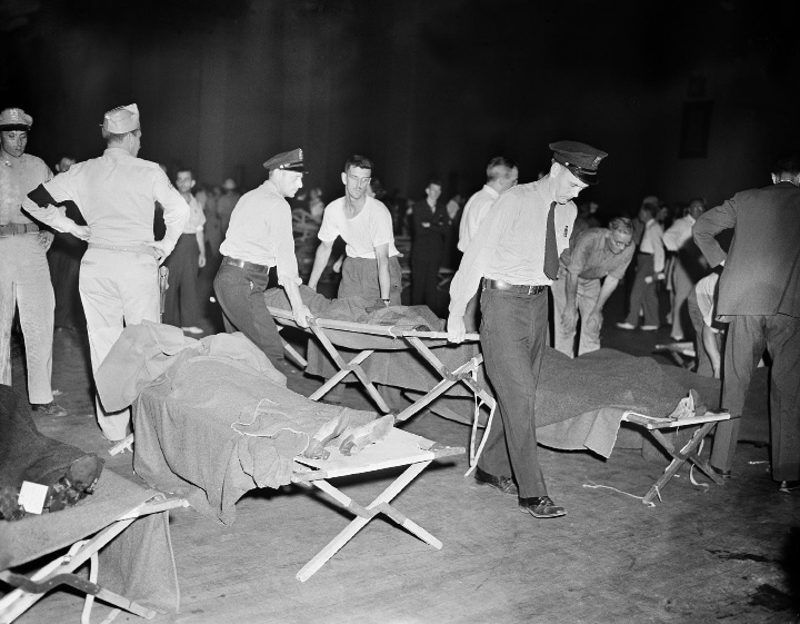 Rescue workers bring the bodies of victims of the circus blaze into an emergency morgue set up in the Hartford, Connecticut armory, July 6, 1944. The fire occurred during the afternoon performance of the Ringling Bros. and Barnum and Bailey show. (AP Photo/Murray Becker)
