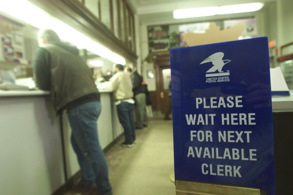 Postal patrons cue up to the counter inside the Meriden post office on Colony Street Wednesday afternoon Jan. 17, 2001. The Ames Plaza branch is now closed.