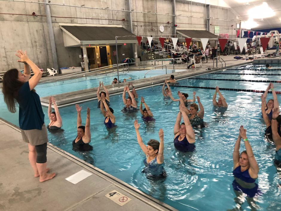 Cammuso has participants raise their arms during the Yoga in the Water class at the Cheshire Community Pool.