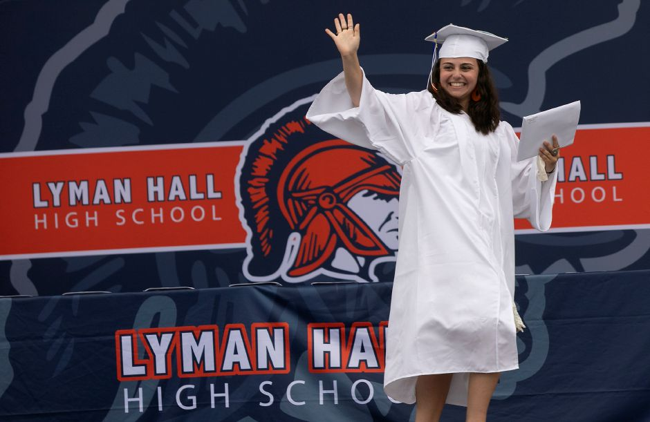 Graduate Maggie Grazioso holds her diploma and waves during Lyman Hall High School graduation ceremonies at the Toyota Oakdale Theatre in Wallingford Tuesday. Photos by Dave Zajac, Record-Journal