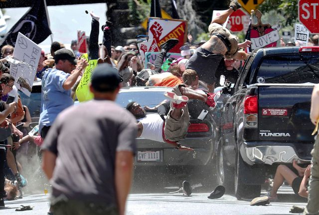 FILE - In this Aug. 12, 2017 file photo, people fly into the air as a vehicle drives into a group of protesters demonstrating against a white nationalist rally in Charlottesville, Va. Gov. Ralph Northam said some of the rhetoric used by groups planning to attend a Pro-Gun Rally in Richmond on Monday, Jan. 20, 2020 is reminiscent of that used ahead of the white nationalist rally in Charlottesville in 2017. One woman was killed and more than 30 other people were hurt when a white...