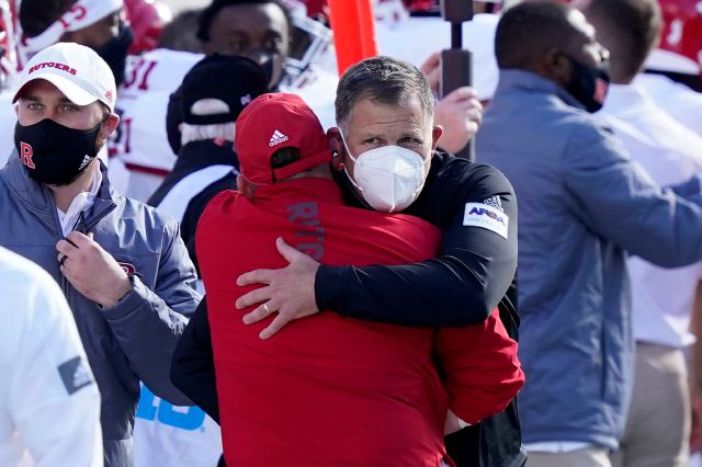 Rutgers head coach Greg Schiano, with a mask, is hugged by an assistant after his team defeated Michigan State in an NCAA college football game, Saturday, Oct. 24, 2020, in East Lansing, Mich. (AP Photo/Carlos Osorio)