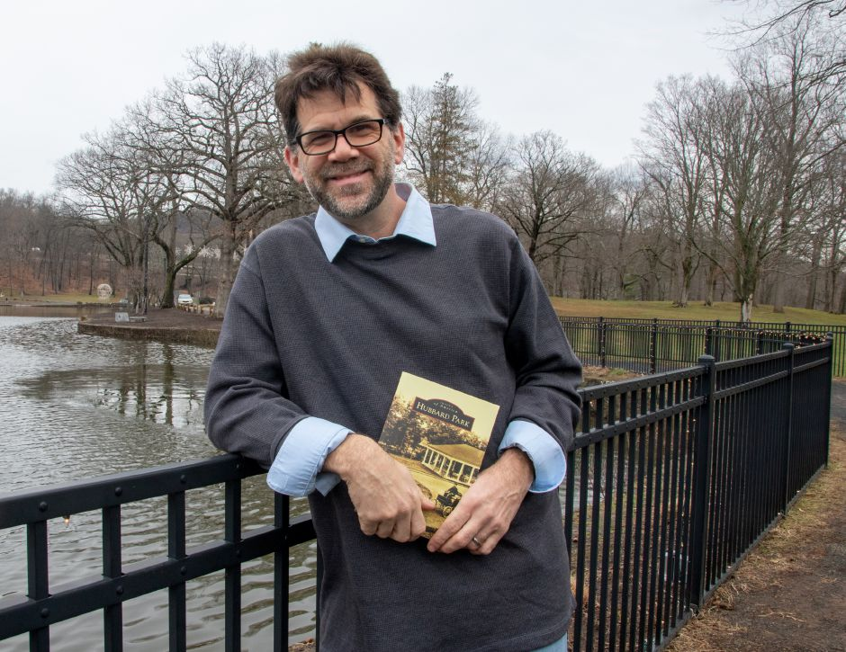 "Justin Piccirillo next to Mirror Lake at Hubbard Park in Meriden on December 31, 2020, with his book ""Hubbard Park"" published by Images of America. Aaron Flaum, Record-Journal"