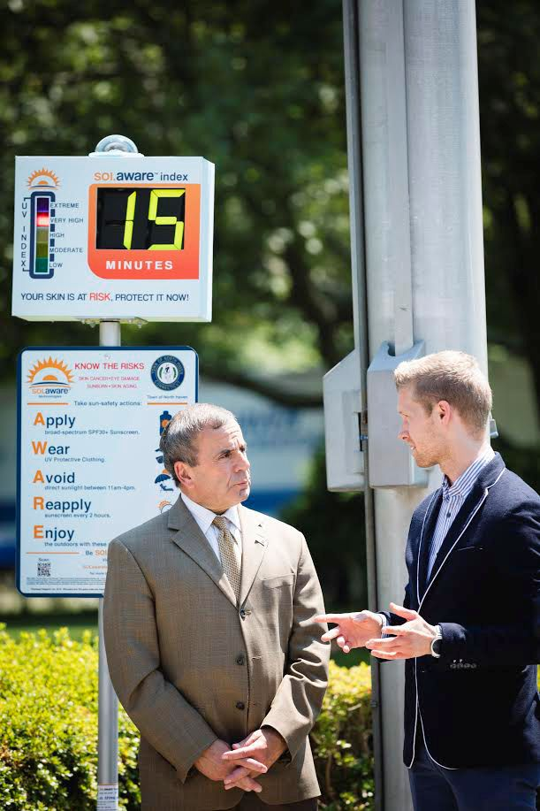 Quinnipiac School of Business graduate Ferenc Fazekas, right, demonstrates his device, SOLaware, to North Haven First Selectman Michael Freda on the Town Green on Monday. Courtesy of  Richard Petrosino, Quinnipiac University