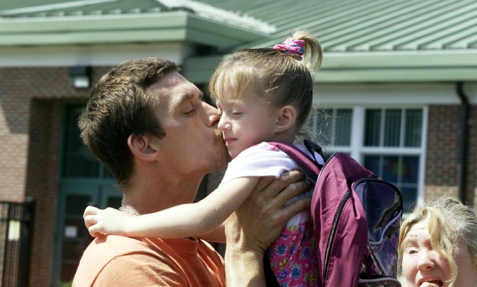 Robert Vickery gives his daughter, Christina Kniffin - Vickery, 5, a kiss before her first day in kindergarten at John Barry Elementary School in Meriden Aug. 29, 2000.