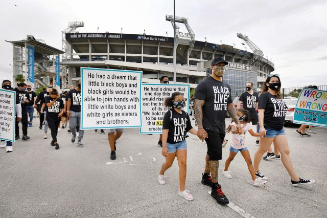 Jacksonville Jaguars assistant defensive line coach Dwayne Stukes walks with his family near the front of the line of players, staff and family members as they start a march from TIAA Bank Field to the Jacksonville Sheriff