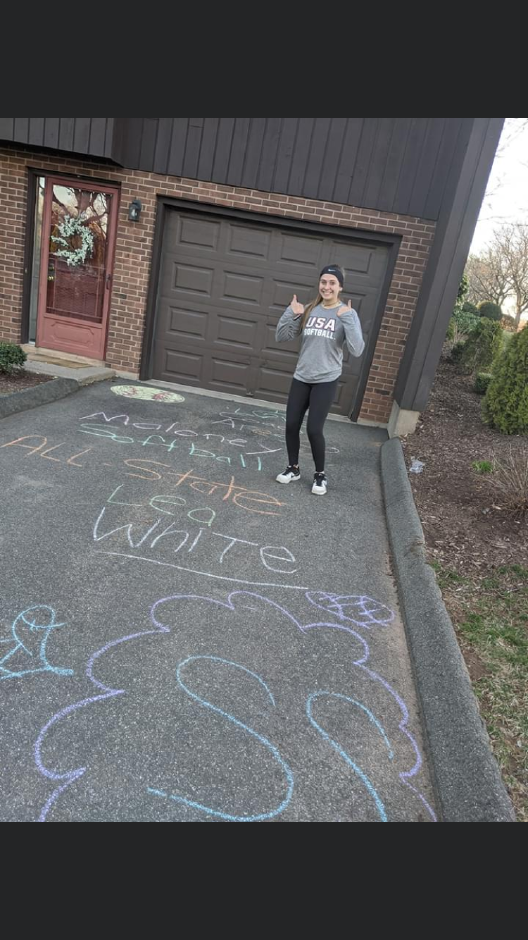 Maloney shortstop Lea White stands alongside the chalked messages left in her driveway by her coach, Scott Aresco, and his three kids. | Photo courtesy of Lea White