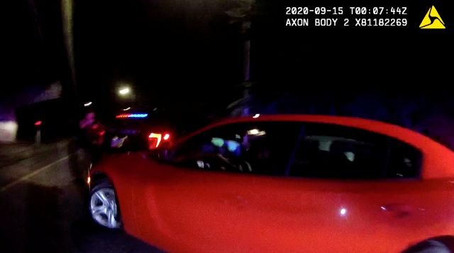 In this Monday, Sept. 14, 2020 image taken from Naugatuck Police Department body camera footage, a car driven by Roznovsky Machado drives toward Naugatuck police Sgt. Nicholas Kehoss, left, during a traffic stop in Naugatuck, Conn. Mercado, accused of driving at a Connecticut police officer who opened fire at the car as it fled a traffic stop, turned himself in Friday, Sept. 18, 2020, and was charged with assault and other crimes. Kehoss, a 10-year veteran of the department, was treated...