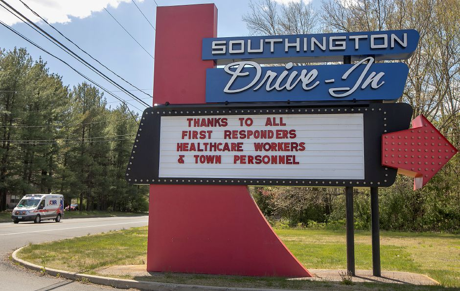 In this Tuesday, May 12, 2020, photo, the Southington Drive-In displays a message to first responders, healthcare workers and town personnel as an ambulance heads to a call on Meriden Waterbury Turnpike in Southington, Conn. Town leaders may announce this week whether the drive-in will open. (Dave Zajac/Record-Journal via AP)