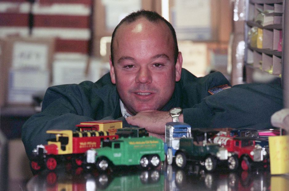 Bill Carlson poses with some of his miniature oil trucks at Carlson oil in Meriden Oct. 15, 1999