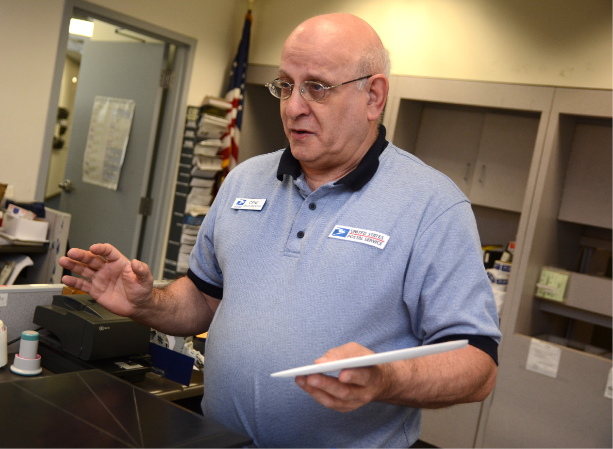 Meriden United States Postal Service clerk Gene Kirsten assists a customer at the post office on Thursday. Kirsten will mark 36 years at the post office on June 27, and will retire three days later.| Bryan Lipiner, Record-Journal