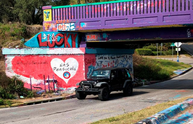 A vehicle drives by a tribute to victims of the Naval Air Station Pensacola that was freshly painted on what's known as Graffiti Bridge in downtown Pensacola, Fla., on Saturday, Dec. 7, 2019. A US official says the Saudi student who fatally shot three people at the Florida naval base had hosted a dinner party earlier in the week to watch videos of mass shootings. The official spoke on condition of anonymity after being briefed by federal investigators. The official says a second Saudi...