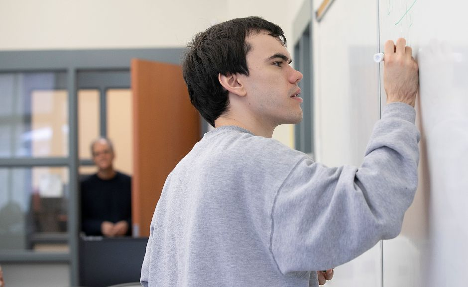 Alex Cable, 26, works on a problem in an Intermediate Algebra class as father James looks on at Tunxis Community College in Farmington, Thurs., Mar. 12, 2020. Alex is one of hundreds of young adults with autism in Connecticut that cannot receive support services from the state due to a lack of funding and a waitlist exceeding 1,600 people. Alex is attending Tunxis Community College in hopes of one-day getting a full-time job. Dave Zajac, Record-Journal