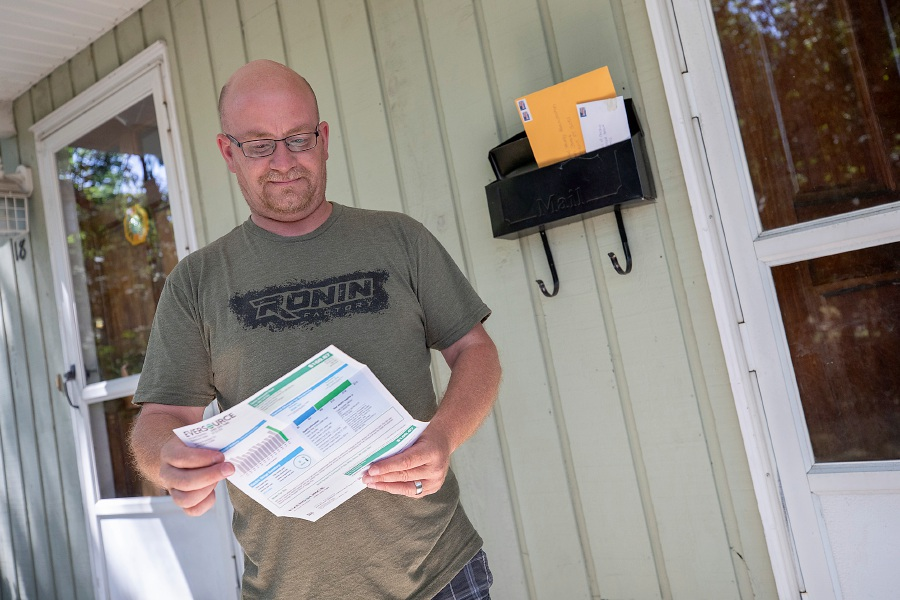 Kevin Casey, of Southington, looks over his electric bill Monday in front of his Visconti Avenue residence. Casey was shocked at the steep spike in the delivery rate from Eversource. Dave Zajac, Record-Journal