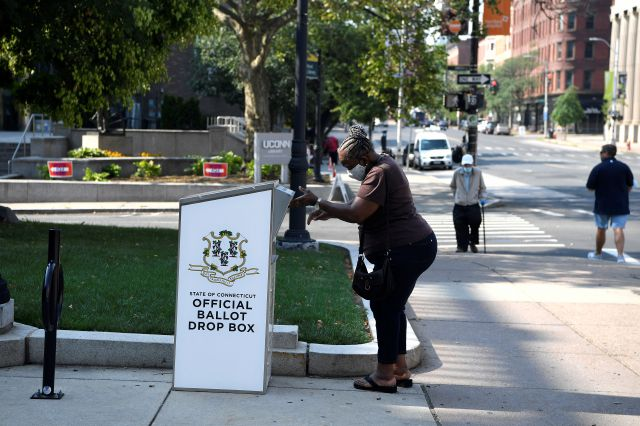 CORRECTS CITY TO HARTFORD INSTEAD OF GLASTONBURY - A woman drops a ballot into a box outside Hartford City Hall, Tuesday, Aug. 11, 2020, in Hartford, Conn. (AP Photo/Jessica Hill)