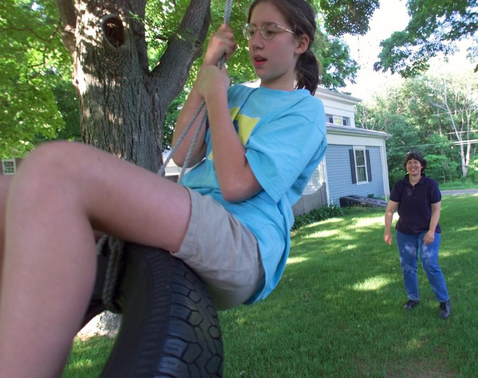 RJ file photo - Annie Fisher, 10, swings on a tire swing in her yard after getting a push from her mother Mary Susan Sabol, right, Tues., June 15, 1999. Sabol and her family are hosts to an inner city girl who will be arriving in July as part of the Fresh Air Fund.