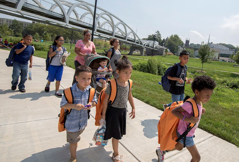FILE PHOTO – Left to right, Manuel Lopez, 3, Emily Lopez, 5, and Jackline Riddle, 4, of Meriden, walk the Meriden Green with their new orange backpacks after attending the annual Back-to-School Expo, Tuesday, August 22, 2017. | Dave Zajac, Record-Journal