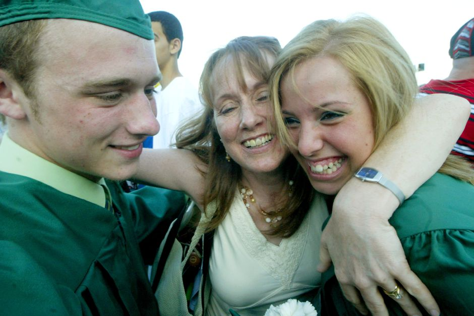 Record Journal Photo/ Johnathon Henninger 6.18.07 left to right, Eric Bergeron hugs his mother, Karen Bergeron and friend Katy DeRosa at the Maloney High School Graduation in Meriden Monday afternoon.