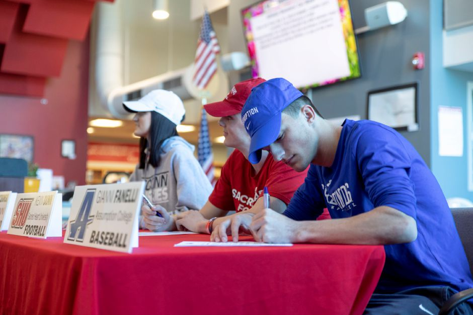 Berlin High School students, from left to right, Patty Mrockowski, Kevin Dunn, and Gianni Fanelli signed letters during an April 4, 2019 ceremony to play sports at the collegiate level. | Devin Leith-Yessian/Berlin Citizen