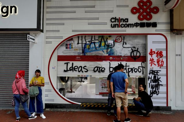 Staff from China Unicom mobile network clean outside the shop as it was damaged during a weekend protest in Hong Kong, Monday, Oct. 7, 2019. Tens of thousands of masked protesters marched defiantly in the city center Sunday, but the peaceful rallies quickly degenerated into chaos at several locations as hard-liners again lobbed gasoline bombs, started fires and trashed subway stations and China-linked banks and shops. (AP Photo/Vincent Yu)