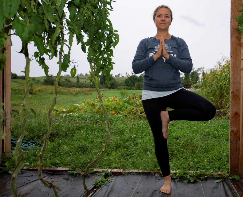 Kelsey Sperl, owner/instructor at Rise Yoga, takes a pose in a greenhouse at Muddy Roots Farm Sept. 10, 2018. | Richie Rathsack, Record-Journal