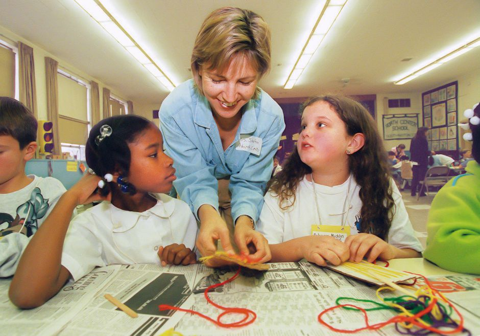 RJ file photo - Parent volunteer Anita Shafran helps third-grade pen pals Arleatha Riddick, 8, left, of Waterbury and Rebecca Michlin, 8, of Southington, with their Latin American loom-woven pendants during the craft segment of North Center School