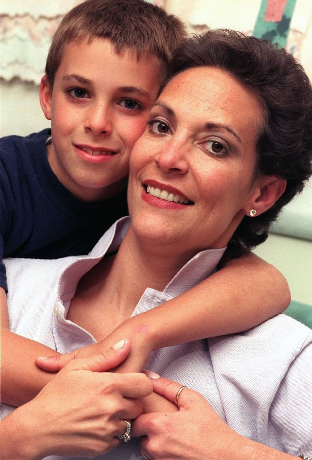 Doreen Nyland gets a hug from her son Nick Nyland, 8, at home in Southington, June 1999.