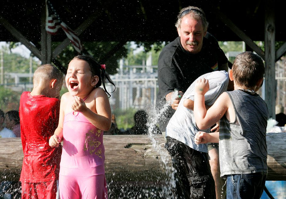 In this 2009 file photo, Mark Albee plays with children at the Annual Summer Barbecue at American Legion Post 45 on Hanover Road. Mackenzie Marquardt, 5, of Meriden runs away from the water while her brothers and friends dart in and out of the water.