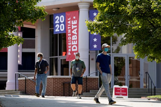 People walk outside the Curb Event Center at Belmont University as preparations take place for the second Presidential debate, Tuesday, Oct. 20, 2020, in Nashville, Tenn. President Donald Trump and Democratic presidential candidate, former Vice President Joe Biden are scheduled to debate Thursday, Oct. 22. (AP Photo/Patrick Semansky)