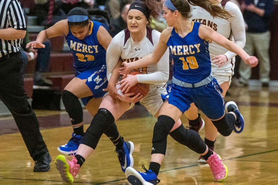 Mercy's Jasmine Mendez, left, and Lauren Kohs try to get the ball from Sheehan's Hayleigh Lagase before Lagase was called for traveling during the second half of Friday's game at Sheehan High School. Aaron Flaum, Record-Journal