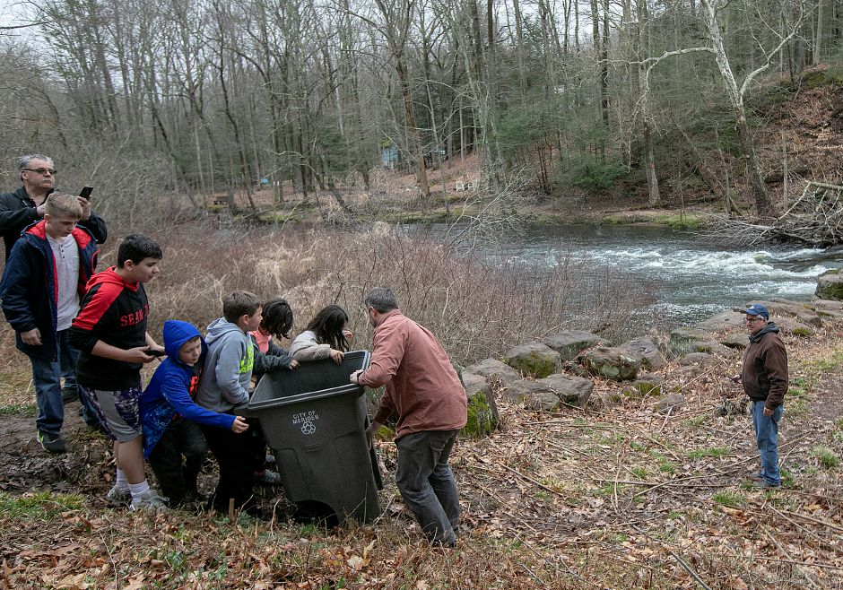 Spencer Meyer, of Guilford, bottom center, helps children carriy a bin containg a large trout to the Quinnipiac River during the annual fish stocking along the Quinnipiac River Gorge Trail in Meriden, Mon., Apr. 8, 2019. Dave Zajac, Record-Journal