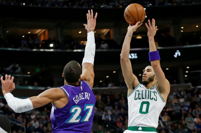Boston Celtics forward Jayson Tatum (0) shoots as Utah Jazz center Rudy Gobert (27) defends during the second half during an NBA basketball game Wednesday, Feb. 26, 2020, in Salt Lake City. (AP Photo/Rick Bowmer)