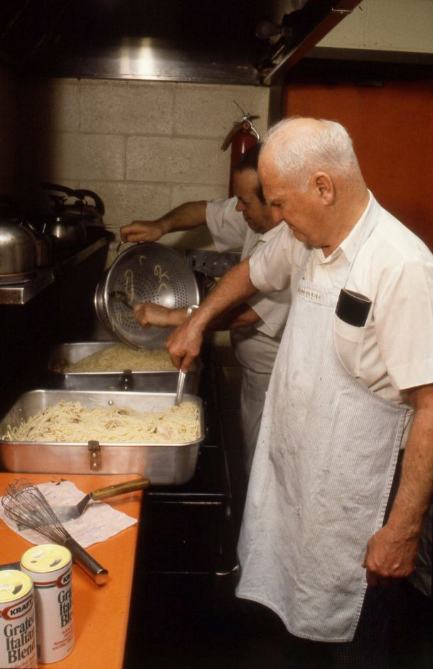 RJ file photo - Henry Drescher, front, and Ernie Garbe, rear, prepare turkey tetrazzini at the Soup Kitchen in Meriden Jan. 25, 1990.