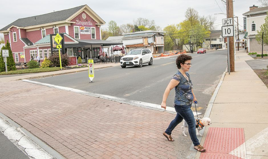 Sarena Salmeri, of Plantsville, crosses West Main Street while walking the Farmington Canal Heritage Trail with dog Riley in Plantsville, Thurs., May 2, 2019. Water main replacement work will begin in downtown Plantsville Monday. Dave Zajac, Record-Journal