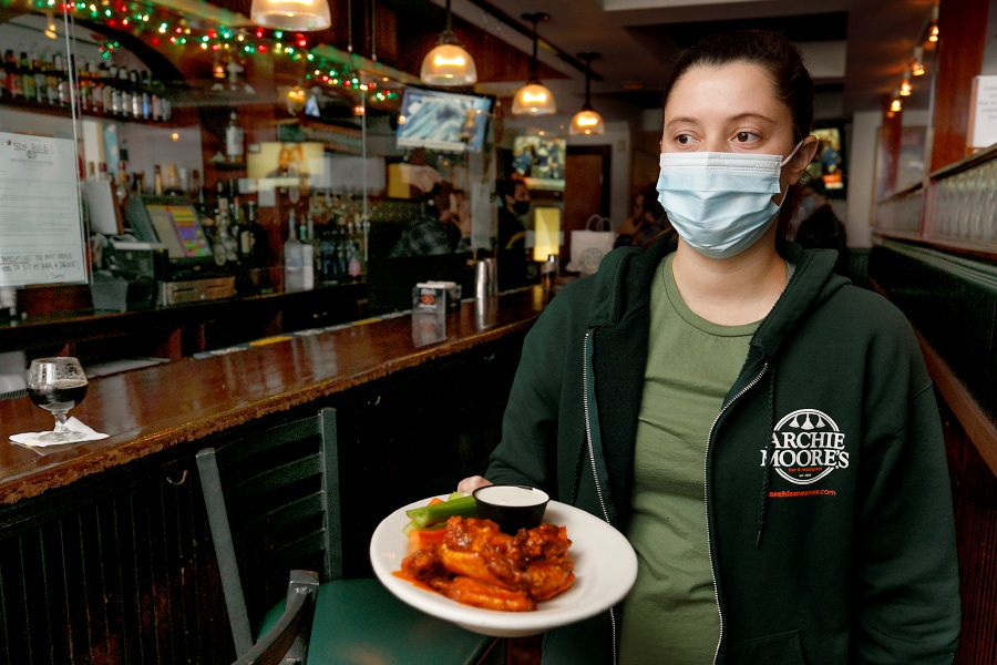 Waitress Christina Ward carries a plate of hot Buffalo wings to a customer on Tuesday at Archie Moore's, 39 N. Main St., Wallingford. Gov. Ned Lamont announced Monday he would be relaxing the restrictions for restaurants. The curfew for restaurants has been extended to 11 p.m. Dave Zajac, Record-Journal