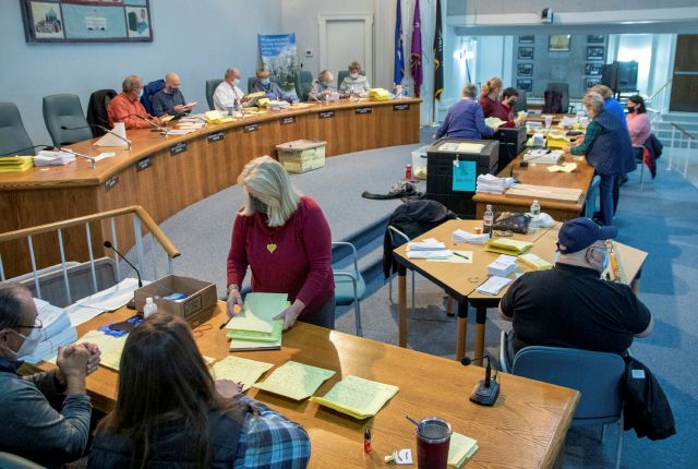 Volunteers work on counting absentee ballots at the council chambers inside the Wallingford Town Hall on Election Day,  Tuesday, Nov. 3, 2020 in Wallingford, Conn.   (Aaron Flaum /Record-Journal via AP)
