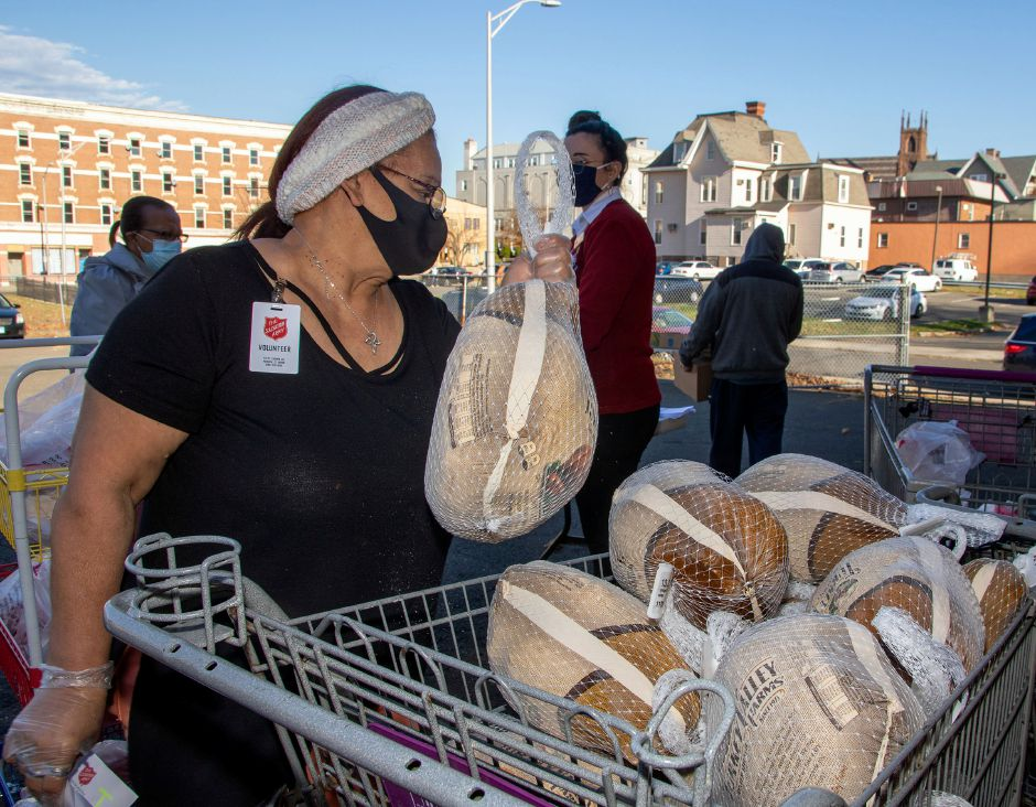 Volunteer Primy Rivera pulls a turkey out of a shopping cart as Thanksgiving meals are distributed to families at the Meriden Salvation Army on Friday, November 20, 2020. Aaron Flaum, Record-Journal