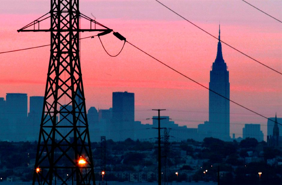 FILE - In a Friday, Aug. 15, 2003 file photo, the Empire State Building towers over the skyline of a blackout-darkened New York City just before dawn. Power lines from Jersey City, N.J., are in foreground. Ten years after a blackout cascading from Ohio affected 50 million people, utilities and analysts say changes made in the aftermath make a similar outage unlikely today, though shifts in where and how power is generated raise new reliability concerns for the U.S. electric grid system. (AP Photo/File, George Widman, File)