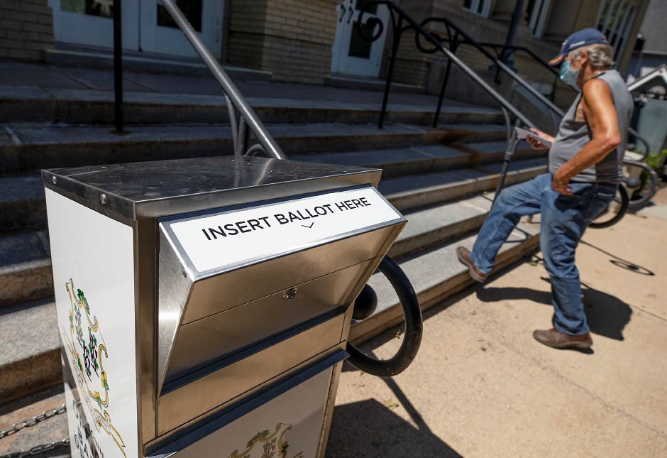 A man walks past an official ballot box in front of Wallingford Town Hall, Mon., Aug. 3, 2020. Public Works crews installed two absentee ballot drop boxes outside Town Hall Monday, after a back-and-forth between the mayor and the state about drop box accessibility for next Tuesday's primary election. Dave Zajac, Record-Journal