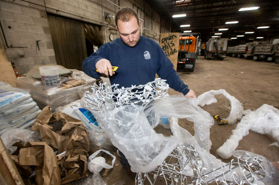 Erik Santarsiere unwraps a horse lighted display from artist Milt Neeley of Utah Wednesday at the Southington Highway Department Garage in Southington November 21, 2018 | Justin Weekes / Special to the Record-Journal