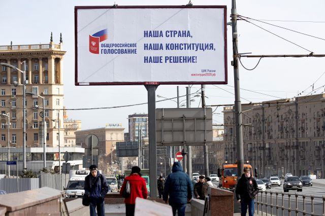 "FILE - In this March 25, 2020, file photo, people walk past a billboard reads ""Our country, our constitution, our decision"" in a street in Moscow, Russia. Russian President Vladimir Putin is just a step away from bringing about the constitutional changes that would allow him to extend his rule until 2036. The vote that would reset the clock on Putin's tenure in office and allow him to serve two more six-year terms is set to wrap up Wednesday, July 1, 2020. (AP Photo/Alexander..."