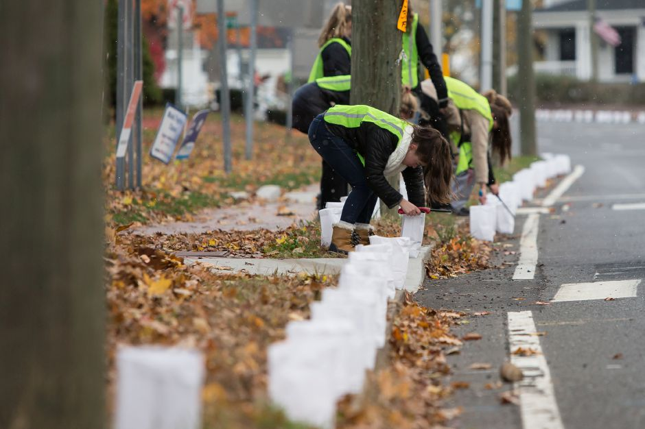 Jenna Kemp 14 of Cheshire sets up a string of luminaries with other volunteers along Route 10 Saturday during the 14th Annual Cheshire Lights of Hope to raise money for local charities in Cheshire November 10, 2018 | Justin Weekes / Special to the Record-Journal
