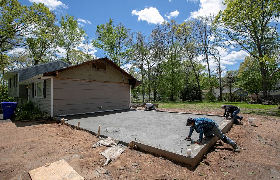 Masons for Onofrio's Total Construction work on the floor of a new garage under construction at 21 Birch Drive in Wallingford on Wednesday. A fallen tree damaged the original garage during last year's microburst.