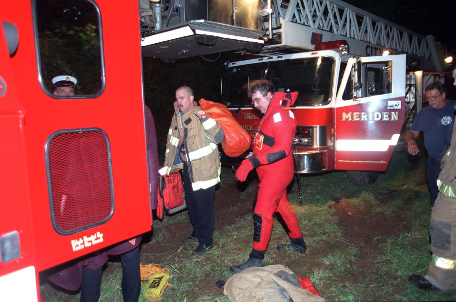 Meriden Fire Department Lt. Brian Giesing, middle, begins to take off his wetsuit after helping in a water resue in the Quinnipiac River Friday night Sept. 17, 1999.