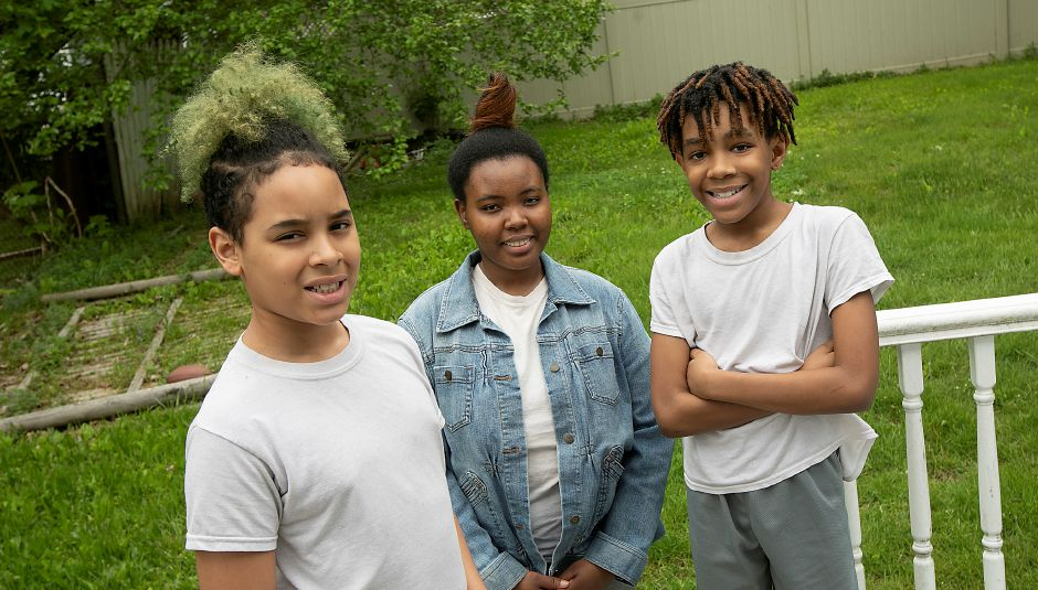 Left to right, Tristan Smith, 10, Sariah Royal, 17 and Zaire Evans, 11, smile in the backyard of their Meriden residence, Fri., May 29, 2020. AT&T donated 100 smartphones to children in the Nutmeg Big Brothers Big Sisters program to make the virtual mentoring program more enjoyable and help them stay connected with their mentor. Dave Zajac, Record-Journal