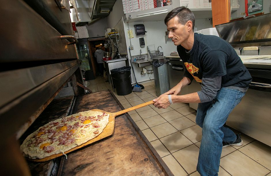 "Chris Laudano, co-owner, slides a ""Flex's Wake & Bake"" pizza made with bacon, eggs and cheese into the oven at Laudano"