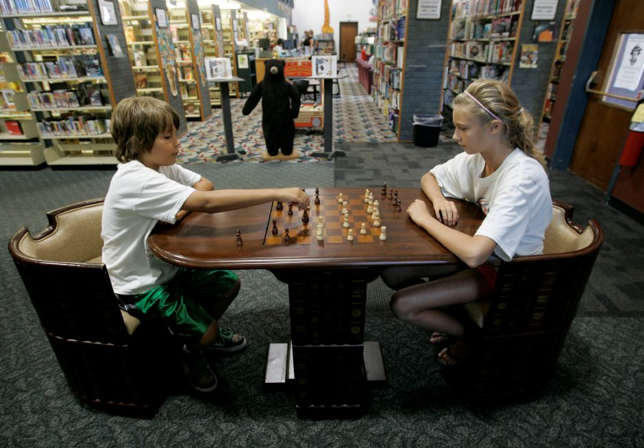 Record Journal Photo/ Johnathon Henninger 8.28.09 - Cousins, Daniel Edgerly, 9, and Jessica Seitz, 11, use chess pieces to play checkers at the Southington public library Thursday afternoon.